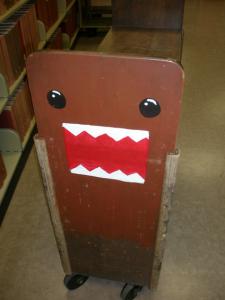 ④UCLAの大学図書館で出会った、あのキャラクター (2007年中川正紀撮影) ブックトラックの側面に日本の某放送局の着ぐるみキャラクター の姿が・・・!もうすでに日本文化の輸出品の一つになっている んでしょうか。いや~、驚きました。思わずシャッターを切って しまいました。あの日本語の決め台詞が現地でも通じるんでしょ うか。今度、試してみようかと思います。